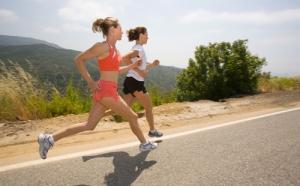 Two women run on road.